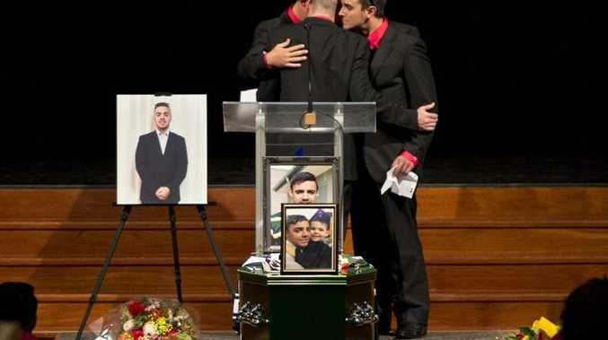 Jeremy Anderson, Mark Duggan, Alex McErlean and Zach Fitzgerald embrace at the funeral of Jaydon Adams.