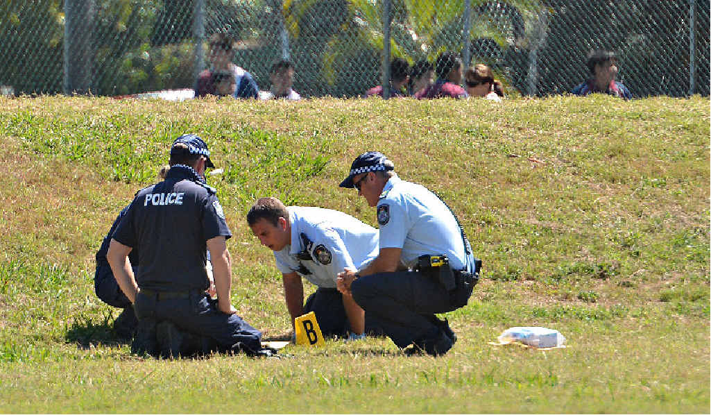 Police inspect an explosive device which was found in the grounds of Mackay State High School.