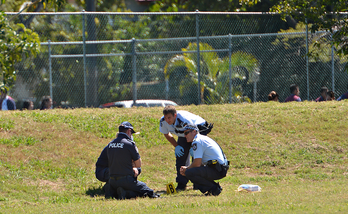Police inspect on of the home-made bombs on the school oval.
