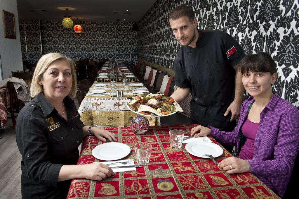 Chef Nazif Gur serves up a platter of char grilled meats to restaurant manager Meral Esenyel and Damla Gur at new Turkish restaurant Efendi's.