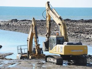Tide washes over excavator stuck in sand at Gatakers Bay