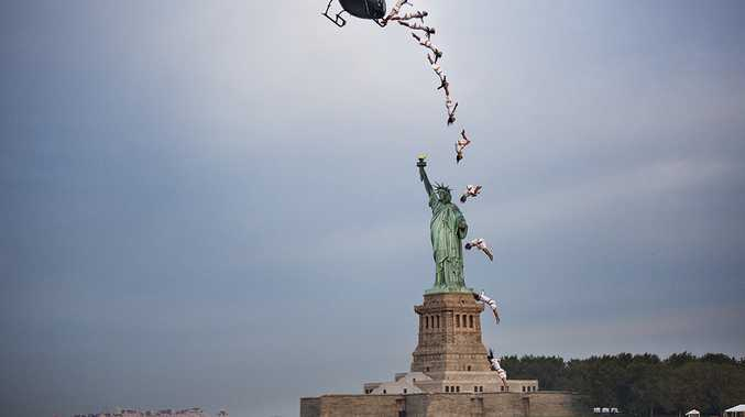 Orlando Duque completes a flying back in front of the Statue of Liberty in New York City, NY, USA on August 19, 2013.