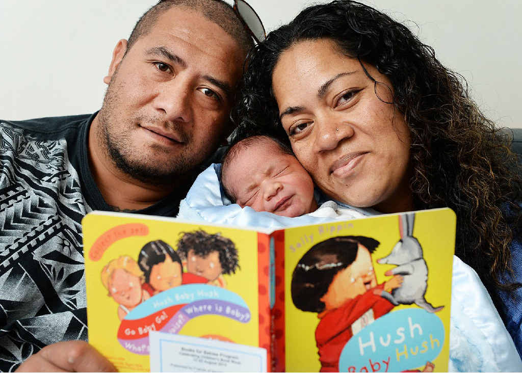 STORY: Johnny and Feofaaki Kavapele read to their new baby Sosefo Maka.