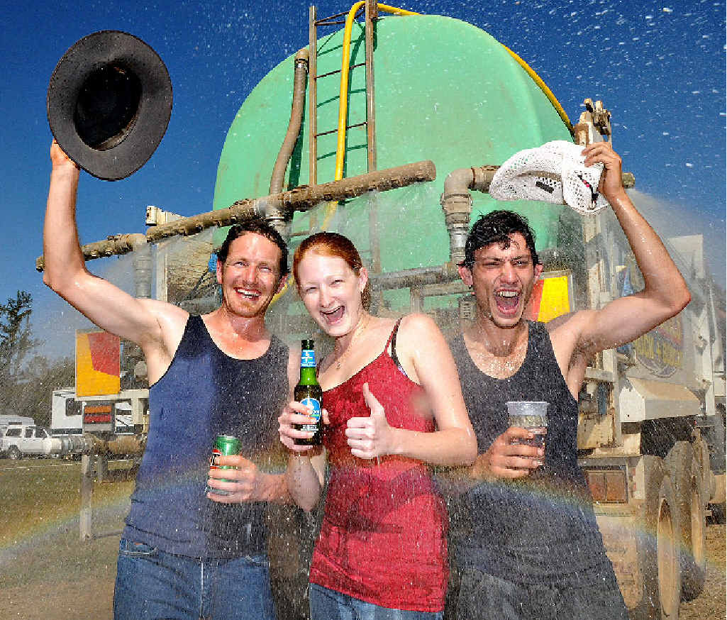 The only way these hard core Muster-goers could cool down in sweltering conditions was to jump under the back of the Campbells water truck. Pictured (from left) is Dave Matthews from Geelong, Neily Bambrick and Yanni Angelo Maltabes, both from Gladstone.