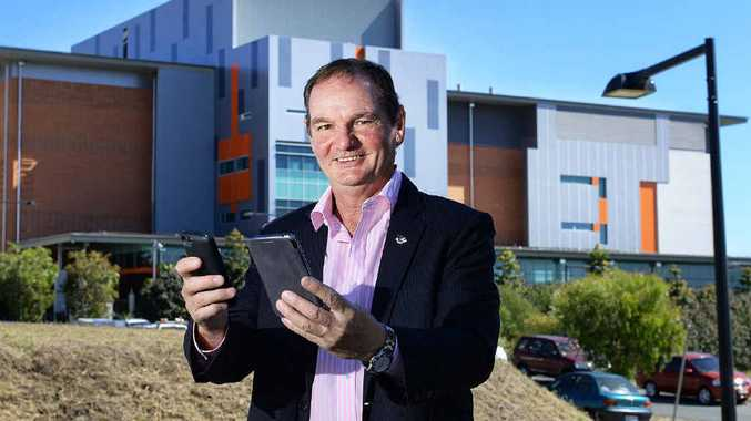 TOMORROW TODAY: Ipswich Mayor Paul Pisasale looks at mobile devices in front of the Polaris Data Centre in Springfield.