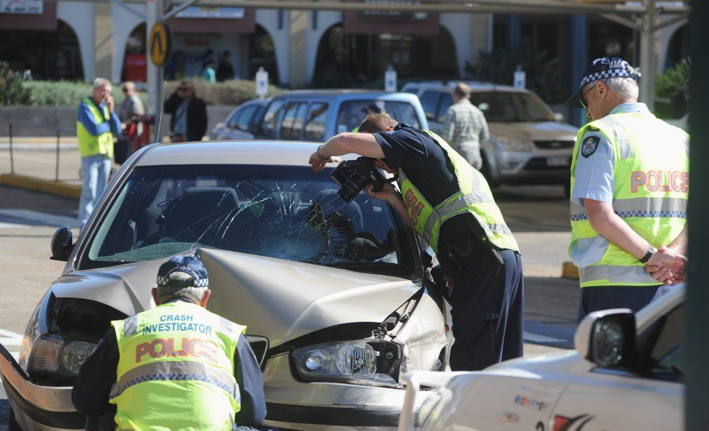 Crash scene investigators examine the car involved in the crash at Woolworths in Pialba last year.