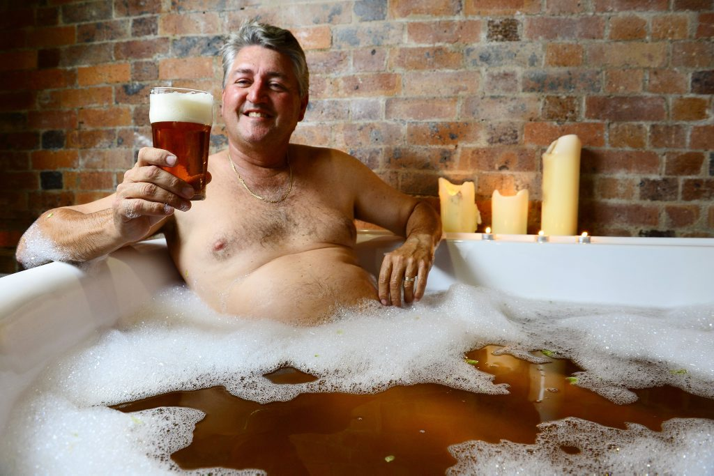 David Glinster enjoys a drink of 4 Hearts Pale Ale and a beer bath at Ipswich Massage and Herbal Spa as part of a special Father's Day gift offer.