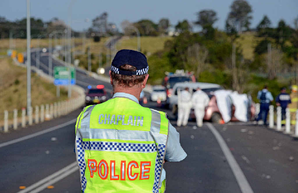 A police chaplain surveys the scene of the crash on the Bruxner Hwy, Wollongbar.