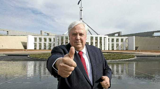 MAN ON THE MOVE: Palmer United Party leader Clive Palmer gestures outside Parliament as he waits to do a television interview in Canberra.