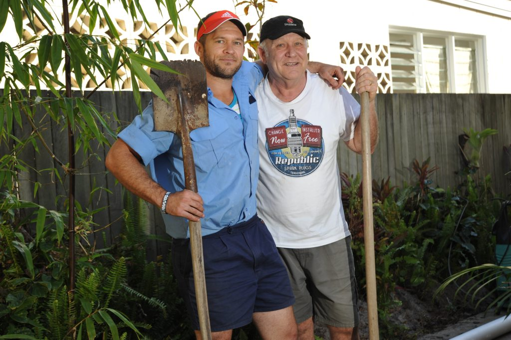 Father and son Gavin and Bradley Smith at the spot they dug up an unexploded shell in the backyard of their Currimundi home. Photo: Iain Curry / Sunshine Coast Daily