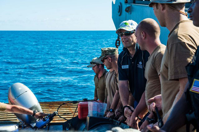 Explosive Ordnance Disposal Mobile Unit sailors with Great Barrier Reef Marine Park Authority advisor Michael Phelan conduct a simulation phase of the jettisoned ordnance recovery in the Great Barrier Reef Marine Park.