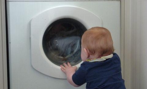 Child fascinated with the washing machine.