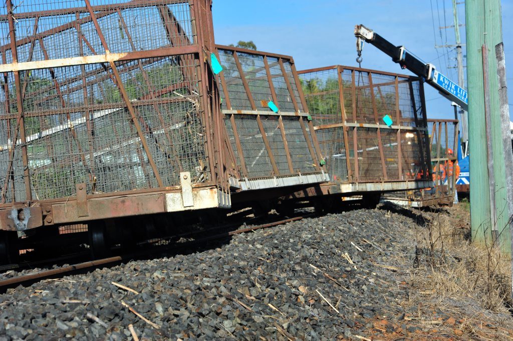 OFF THE RAILS: Bundaberg Sugar works hard to put derailed carriages back on track at South Kolan. Photo: Max Fleet / NewsMail