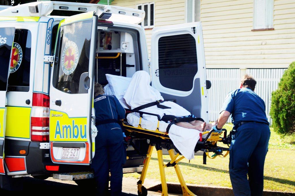 Ambulance officers load an injured man into an ambulance before taking him to Maryborough Base Hospital.