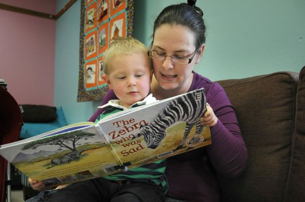 Withcott mum Anita Kruger reads to her two-and-a-half year old son William and five-month-old Nicholas. Research has revealed that only one in four parents read to their children on a regular basis.