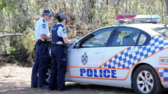 Police vehicles on the property near the Bruce Highway where human remains have been discovered.