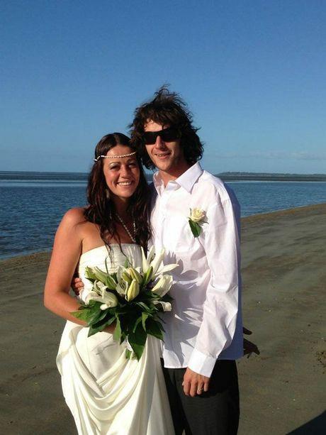 Hervey Bay's Callen White and Germany's Tina Koslowsi tie the knot on Dundowran beach.