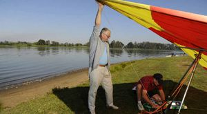 Terry Aspinall, of Brisbane, watches on as pilot Anton King sets up his hang glider ready for a re-enactment at the celebration of 50 years since hang gliding took place on the Clarence River.