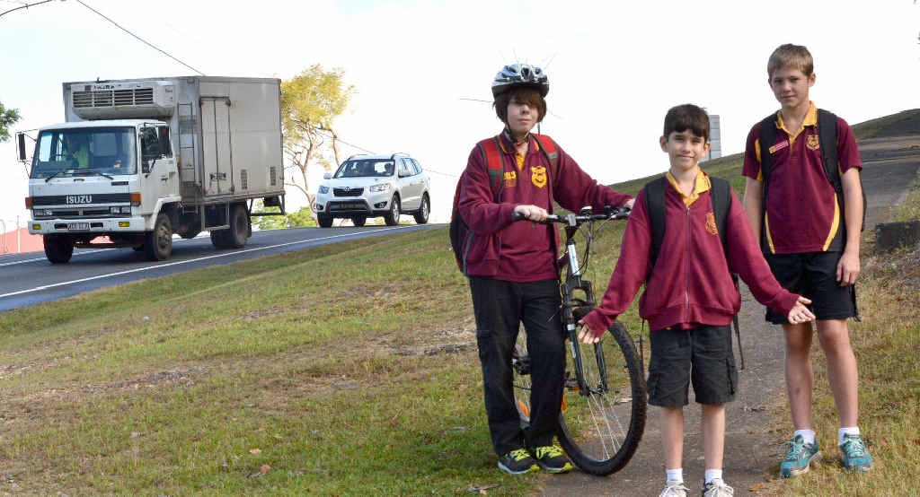 SAFETY CALL: Monkland State Primary School students Joshua McLaughlin, Jack Marshall and Thomas Fea show the end of the walking path before their school and beside a busy Brisbane Rd. Students have petitioned council to complete the walk and riding pathway to make it safer for all members in the community.