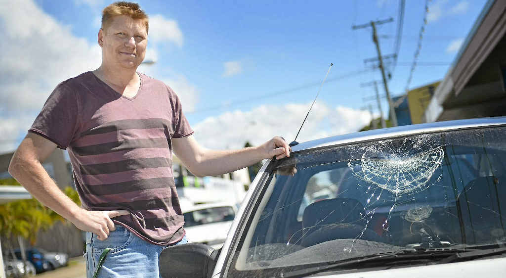 Jarod Foster inspects his car's damaged windscreen on Tank St in Gladstone.