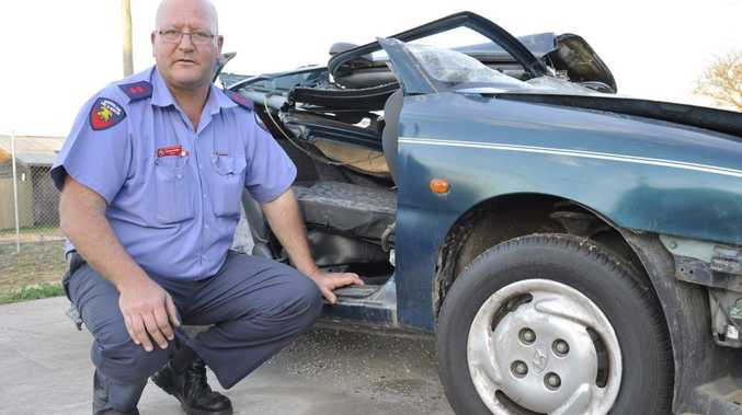 Oakey Fire Station officer-in-charge Captain Rodney Mason inspects a car which has been used for hydraulic cutting tool practice.