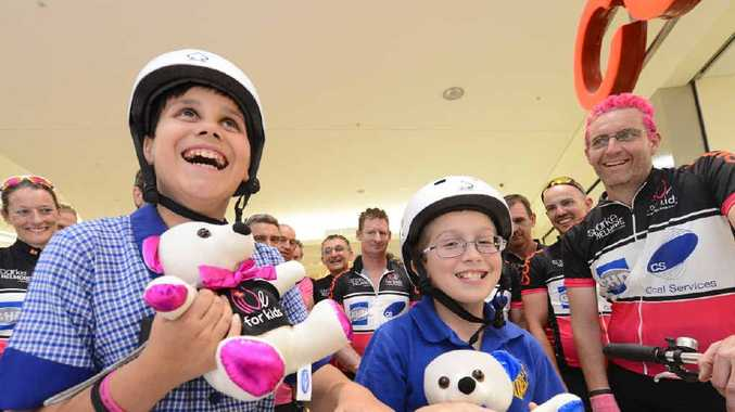 PEDAL POWER: Grafton Public School students May Reilly and Zac West are thrilled with the tandem bike presented by riders of the Live For Kids cycle who stopped at Coles in Grafton Shoppingworld. Photo Adam Hourigan