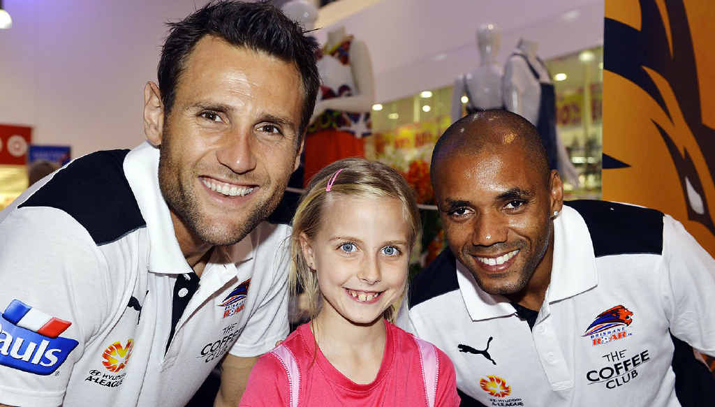 FAN: Krystal Brown, 8, with Brisbane Roar players Michael Theo and Henrique de Andrade at Riverlink Shopping Centre.