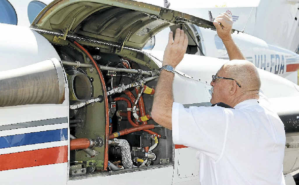 RFDS pilot Graham Vonhoff checks his Beechcraft engine for the last time.