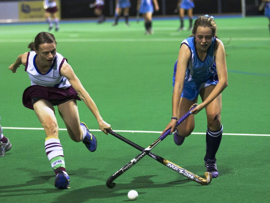 CROSS PURPOSES: McAuley's Ange Day and Grafton High Blues' Taylah Hamilton cross sticks during Saturday night's grand final. Photo: Shane Sedger