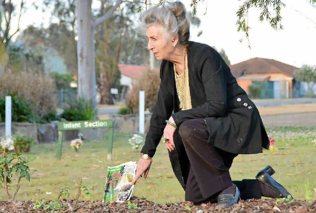 SHOCKED: Sheila Kemp shows her disgust at the site where vandals stole rose bushes from the infant section at the Nanango cemetery.