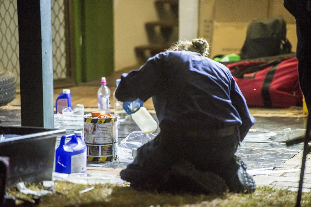 A Senior Constable inspects items found in a Carter Street residence as part of the two drug raids conducted in Gladstone.