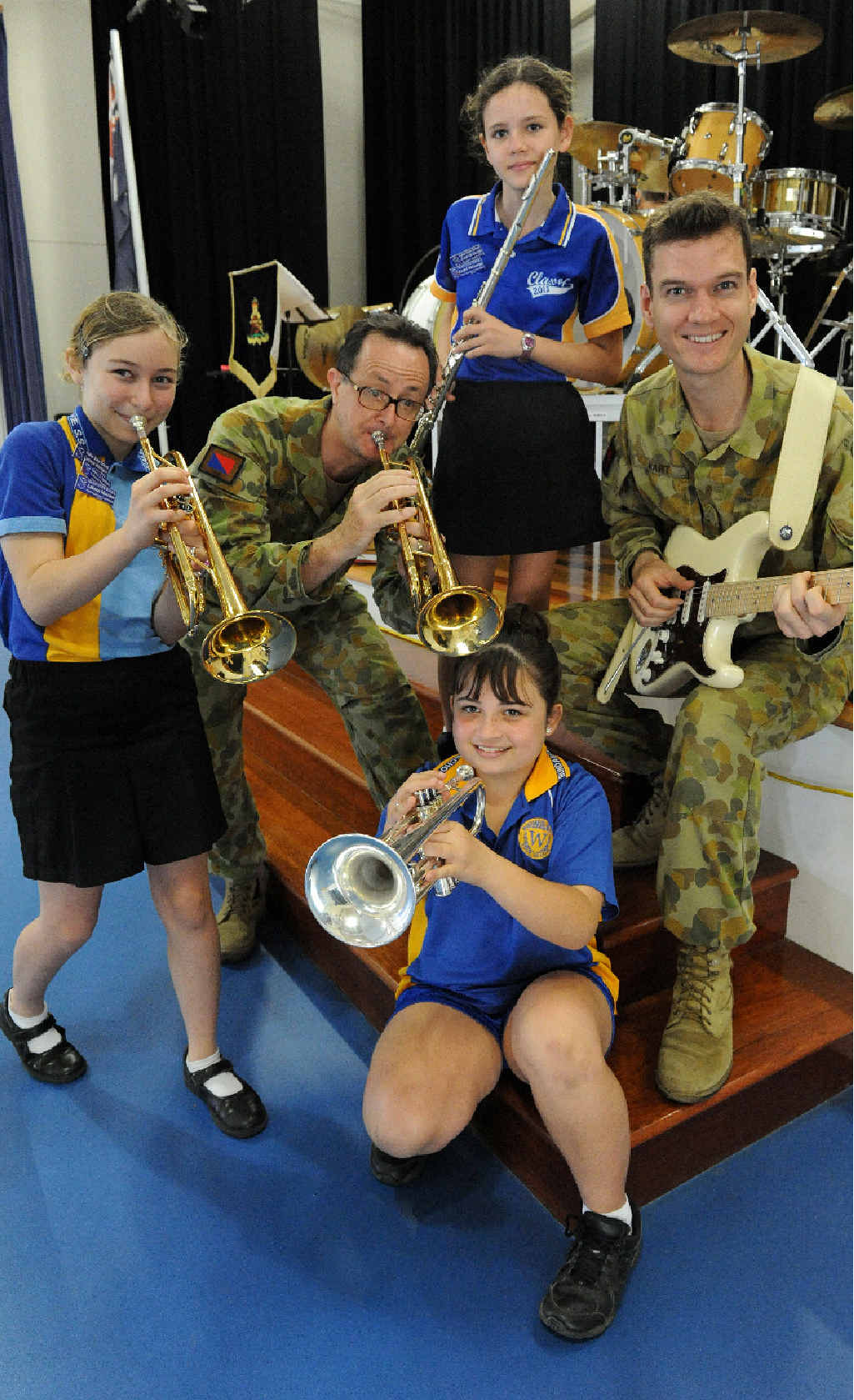 Kalkie State School students Lukaeja Morrison, Matilda Burt and Gretel McGeorge with the 1st Regiment Royal Australia Artillery Band musicians Warren Keir and Frank Hart.