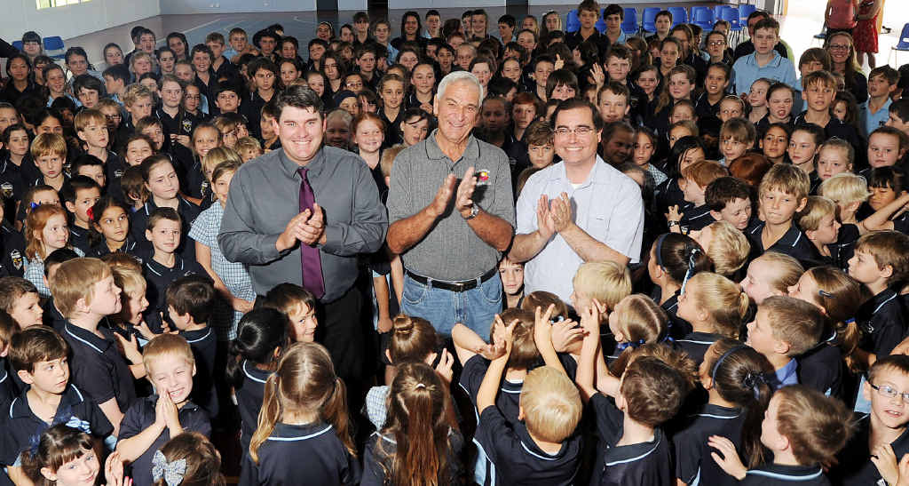 TOP DONATION: St Mary's Primary School students are applauded by Woolworths assistant store manager Grant Ollett, St Vinnies Wayne Lusk and Father Paul Kelly for their efforts raising funds for charity.