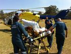 Paramedics wheel a man to the RACQ Careflight Rescue helicopter after a crash at Manar Park motocross track.