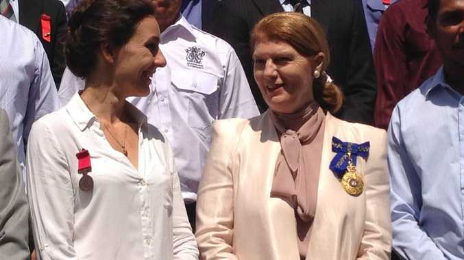 Sarah Norman (left) talks with Queensland Governor Penelope Wensley on the steps of Government House after receiving a bravery award on her brother's behalf. Sarah is the sister of Sam Matthews who saved his family at Murphy's Creek during the 2011 floods. Sam was tragically killed in a fire six months later.