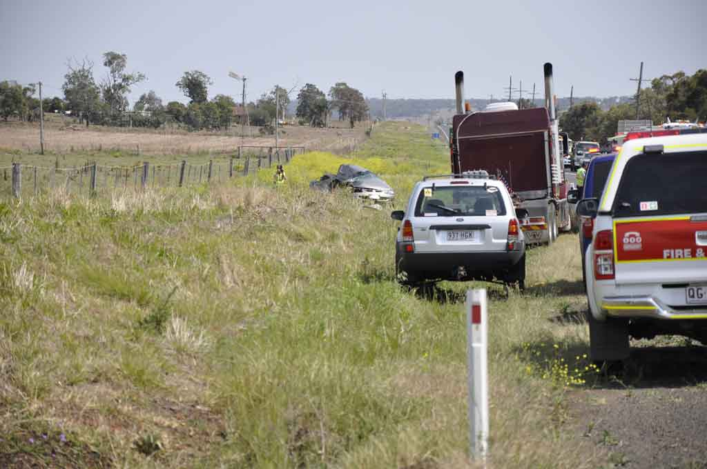 Emergency services at the scene of this morning's fatal traffic crash 20km west of Toowoomba on the Warrego Hwy.