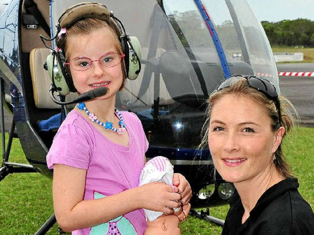 Johanna Osborne from Chopperline helps Jade Scott, 7, get ready for her helicopter flight yesterday.