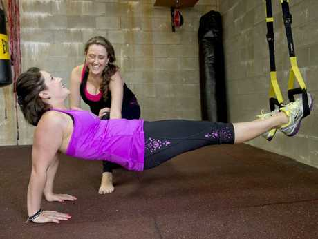 Yoga teacher Kylie Jeffrey instructs Danielle Brown during a yoga session using suspensions at Complete Body Yoga and Fitness.
