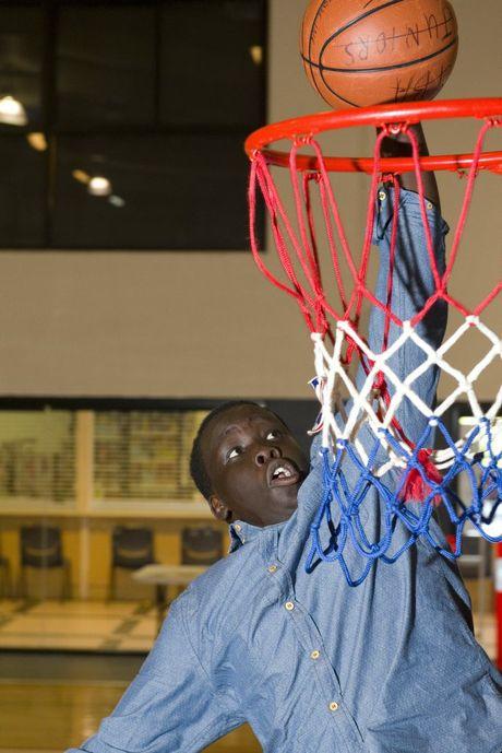 Agok Deng slam dunks in support of Midnight Basketball.