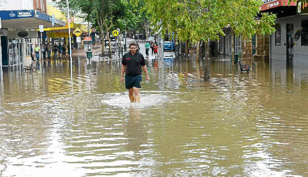 Mary St business owner Peter Kross walks from his flooded business before the last flood clean up.