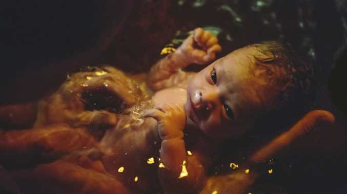 Newborn soaking in birthing pool