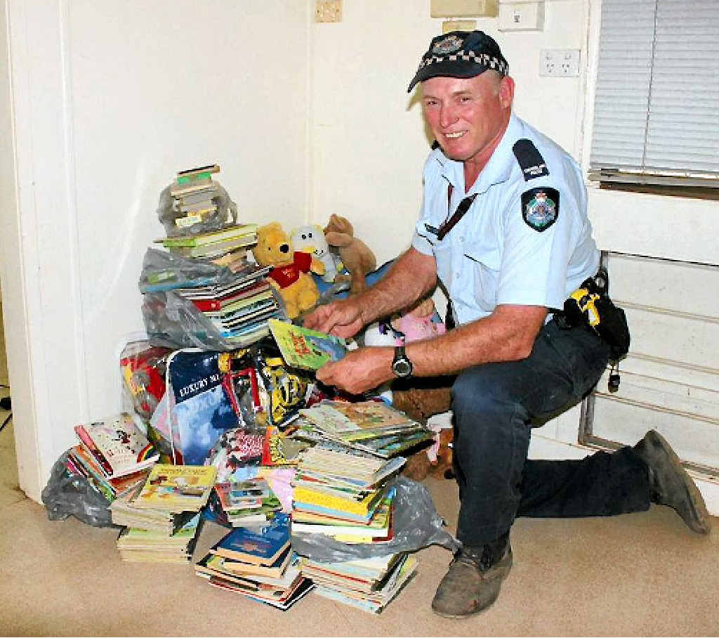 Former Hervey Bay police officer James Hunter with some of the books and toys for the children.