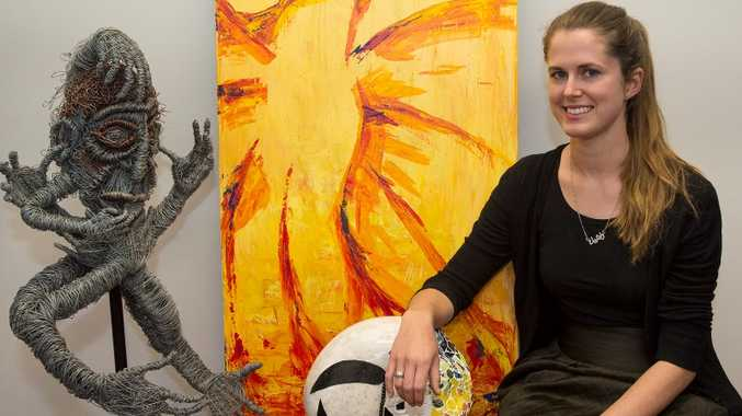 USQ health promotions officer Rachel Hammersley-Mather with a few of the high quality submissions to the University's Mental Health Week art competition.