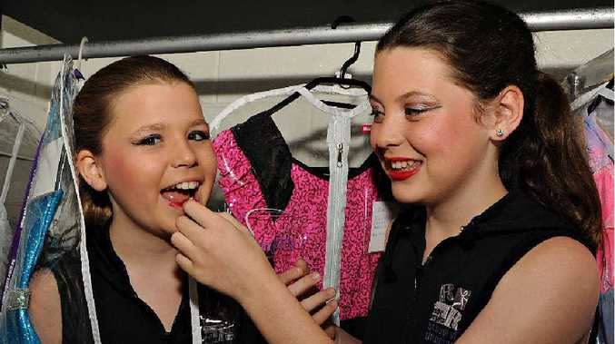 Twins Zodie and Marita Bolic, 11, show off some of the nine costumes they each need to compete in the Mackay Eisteddfod.