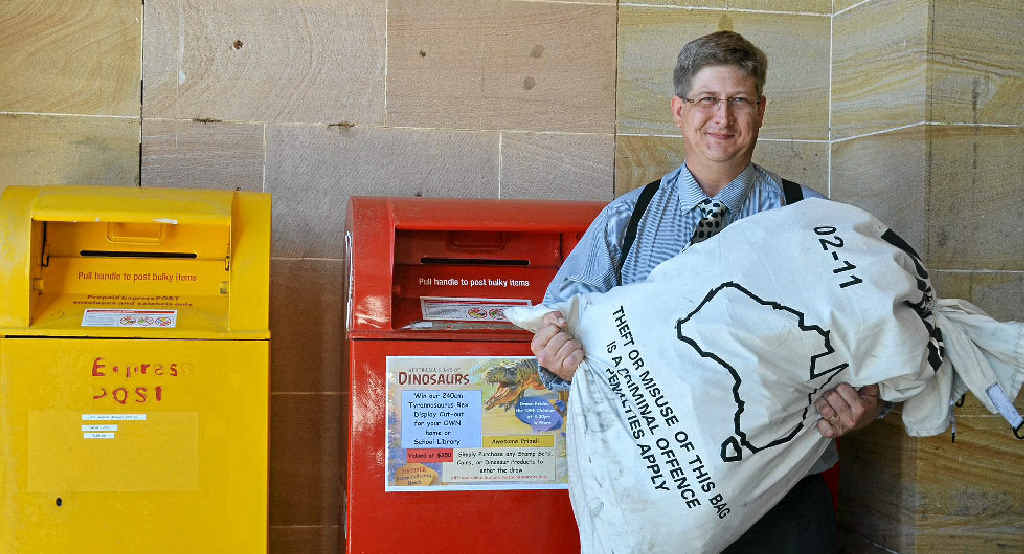 Postal services officer Kyle Hughes with a bag of mail to be sorted at the Warwick Post Office.