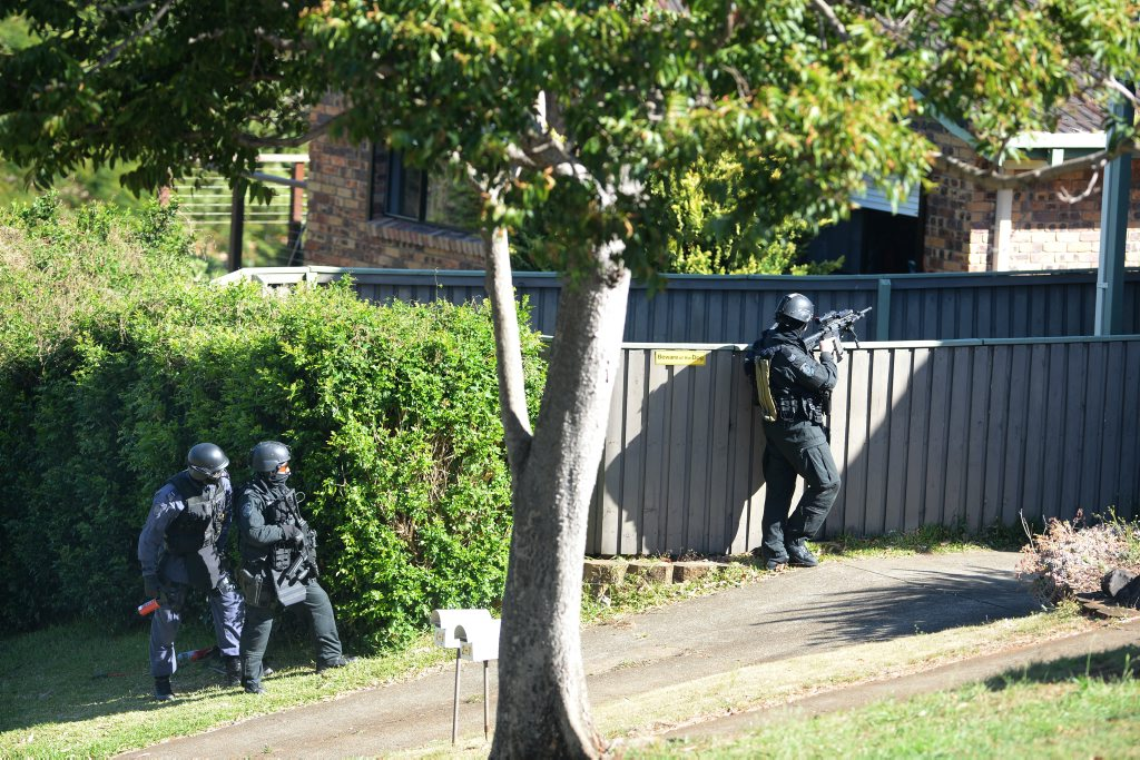 Police surround a house in Banora Point. Daily News