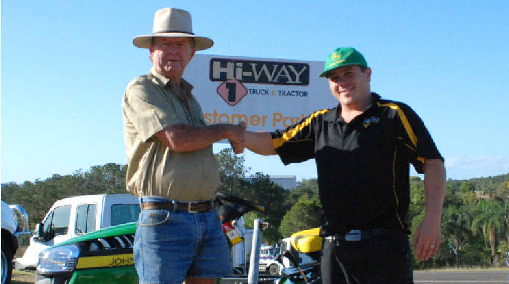 Terry Vollmerhausen receives the keys for his new ride-on lawnmower from Hi-way 1 grounds care specialist John Williams.