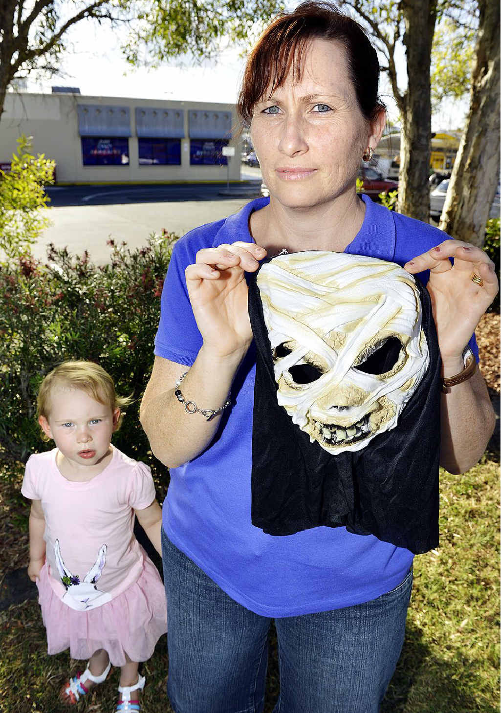 SCARY: Lauren Cochrane holds up a Halloween mask purchased from Just Crazy Bargains in Booval. Mrs Cochrane says the shop's Halloween display reduced her daughter to tears.