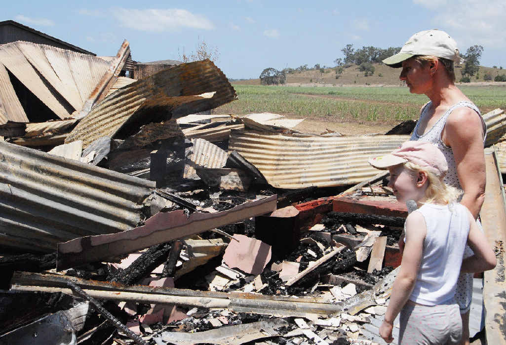 Diane and Bianca Haupt examine the remains of a house on their family's property which burnt down.