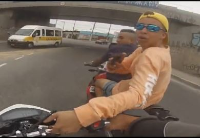 A gunman threatens a motorcyclist in Brazil.